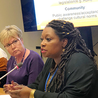 2 women, one on left is more in background and listening, one on right is foreground and speaking