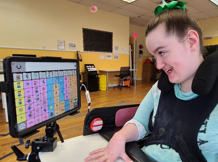 Amelia at her wheelchair, she is looking at the screen of the communication device she is using talk suite on