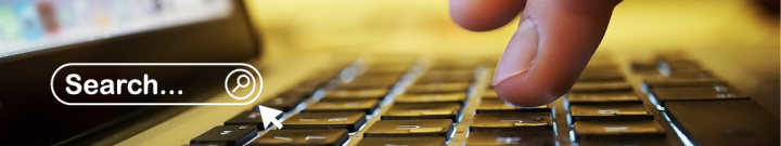 close up fingers over a laptop keyboard with search bar icon overlay