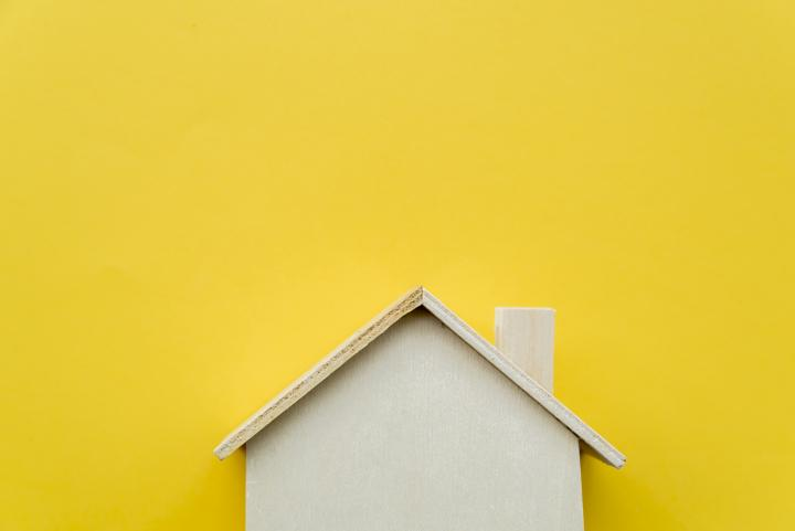 Miniature wooden house with yellow background