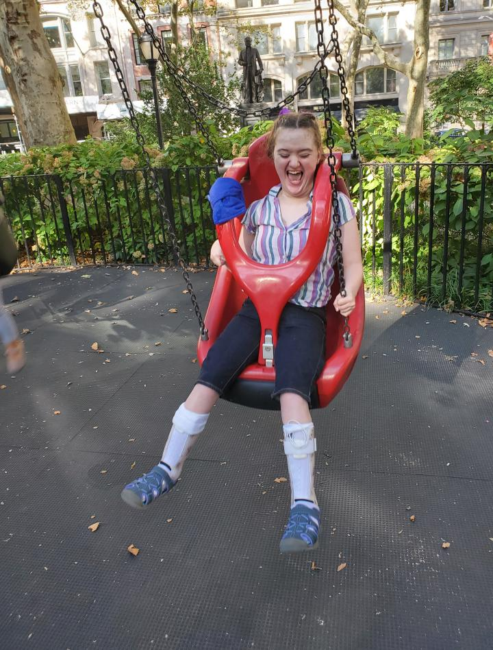 Amelia with a very big smile/laughter is in a red adaptive swing