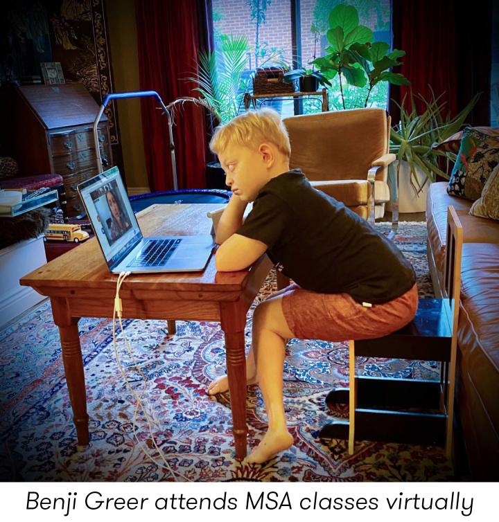 Benji sits at a table at home looking at a laptop