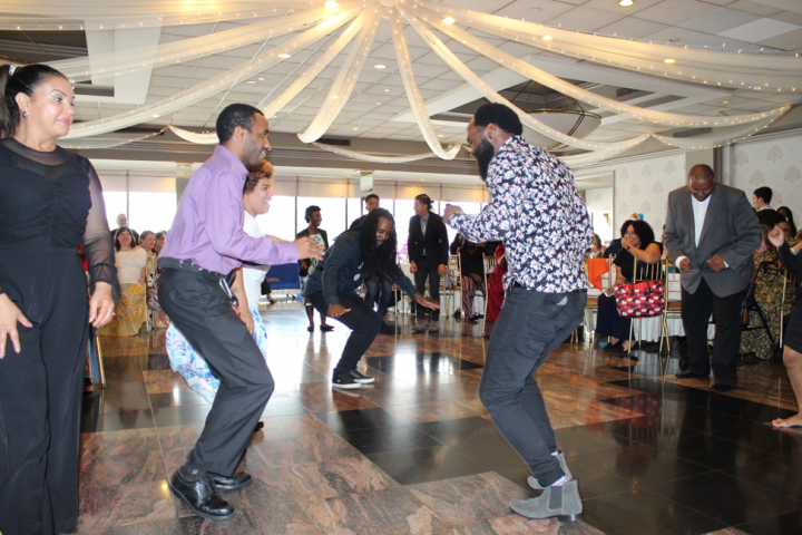 People dancing and smiling. Staff from YAI's Queens region hold a dance-off at last year's DSP recognition event.