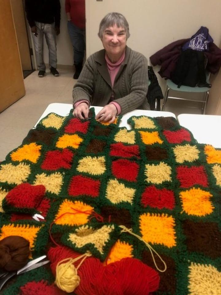 woman with colorful crocheted blanket laid out in front of her
