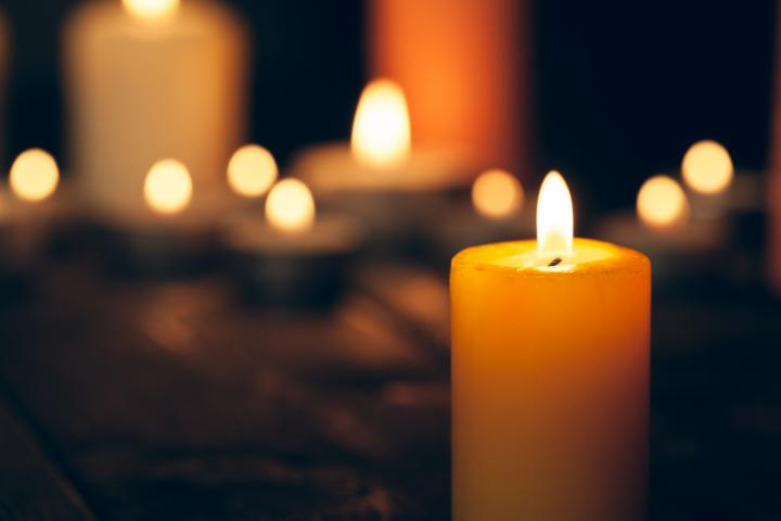 A burning candle in foreground with blurred burning candles behind it in on a black background