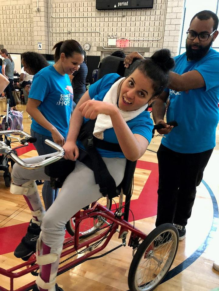 iHOPE student Maria celebrates after she completes an adaptive cycling race.