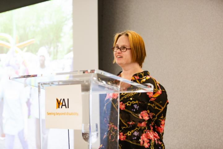 Woman in a floral dress stands at a podium, there is a sign on the front of the podium with the YAI logo on it