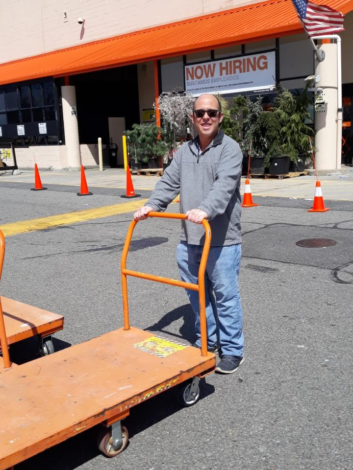 Jordan stands outside hardware store with a flatbed cart