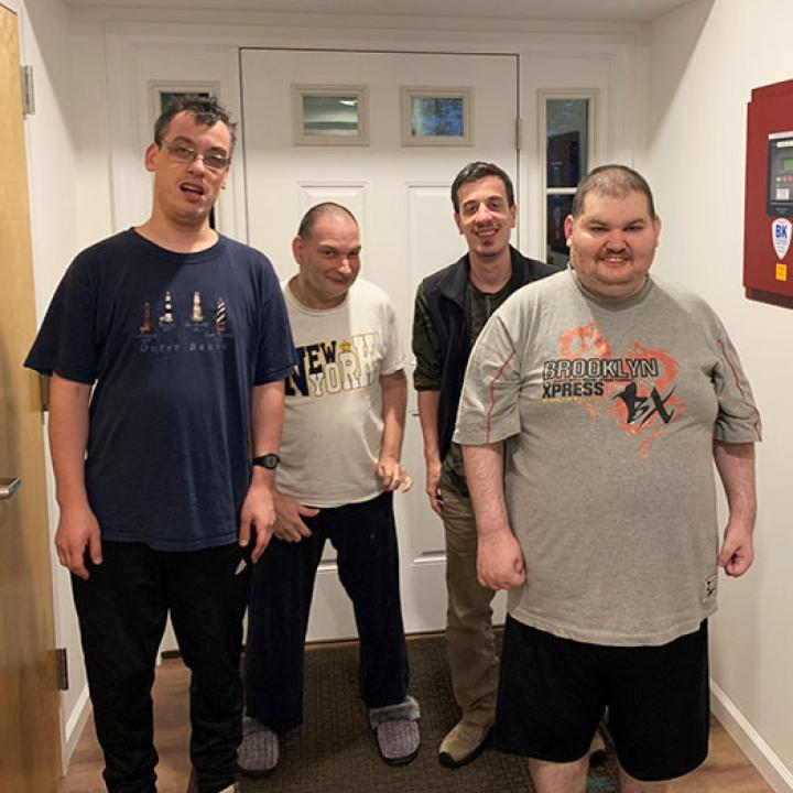 Four men stand inside by a door and pose for picture