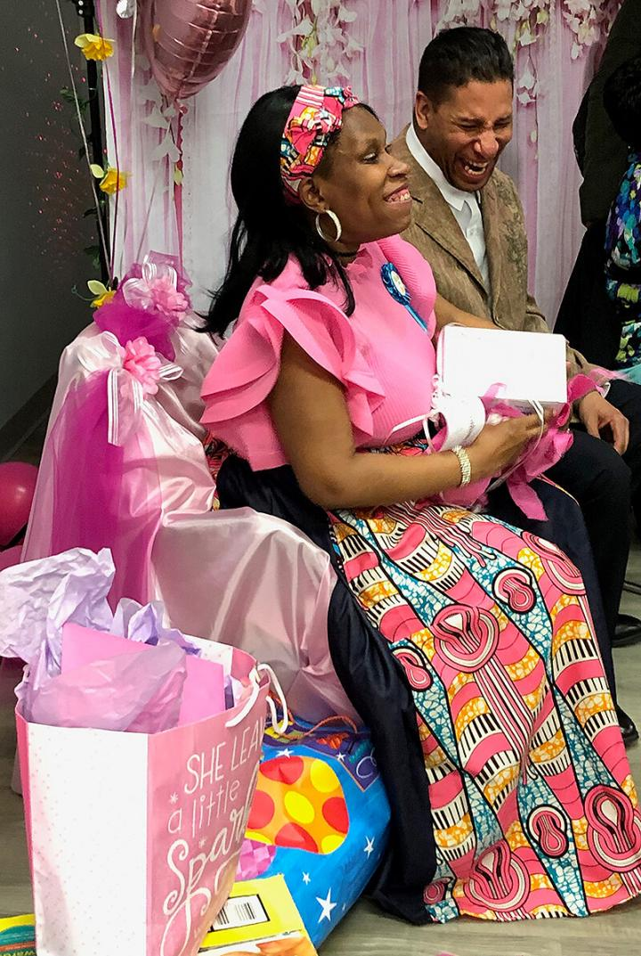 Tanzanika Rosado and her husband open gifts at their baby shower.