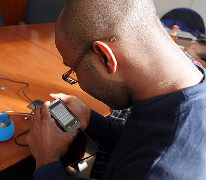 Picture shows a person wearing glasses using a tech device