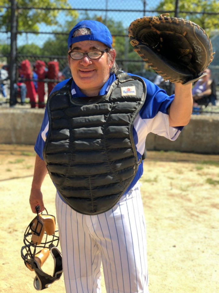 Man stand wearing a baseball uniform and has his left hand up wearing a baseball glove
