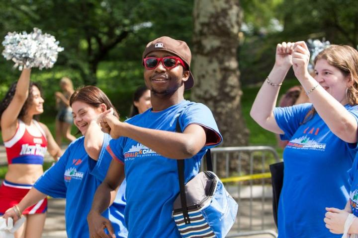 People wearing blue shirts, smiling and walking at central park challenge last year