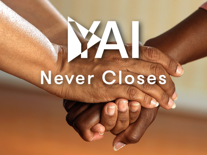 2 hands hold one hand with overlay text YAI Never Closes