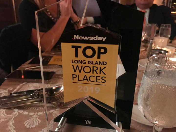 "Award trophy with text ""Newsday TOP Long Island Work Places 2019"""