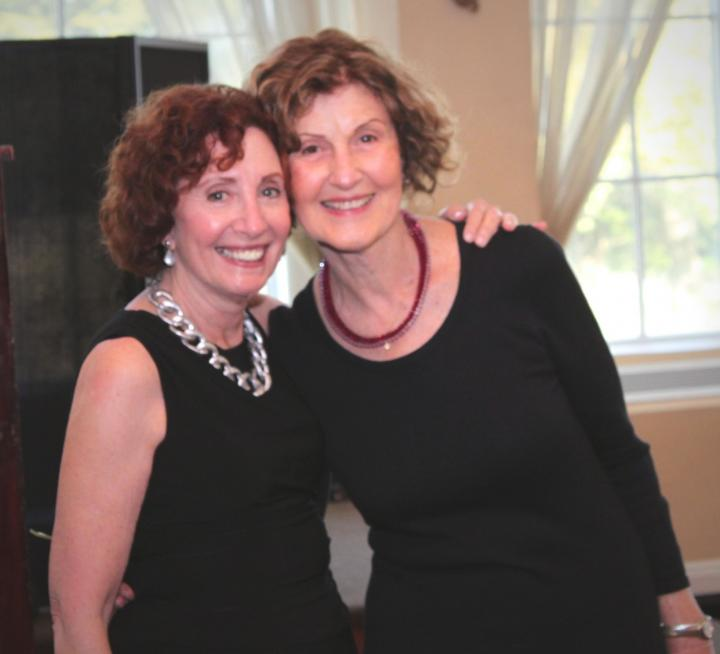 Photograph of two woman wearing black, smiling at the camera