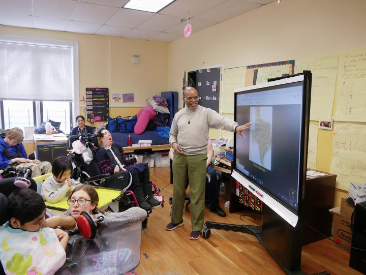 Man stands and points to a smartboard with children and staff in classroom