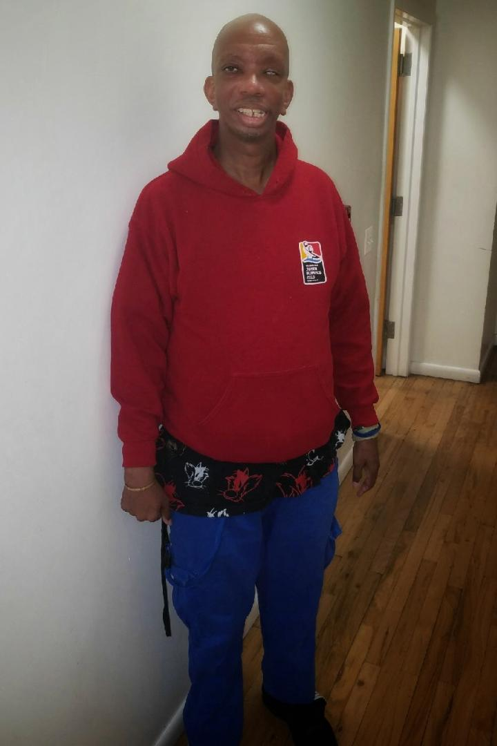 Photograph of Lee, standing and smiling, wearing a red sweatshirt and blue pants