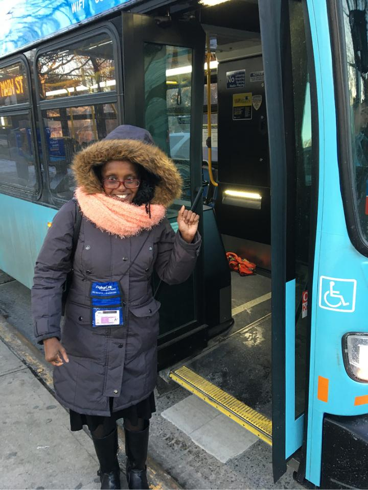 Photograph of Yolanda standing by an NYC bus