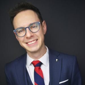 Alek Hoyos wears glasses with a deep blue suit and red and blue large striped tie, he is smiling